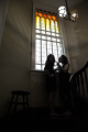 black and white sepia tone gothic stained glass window arches bannister staircase railing forbidding scary creepy dark shadows stool steps two girls young women conversation accusing looking interrupted