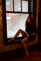 window sitting wooden frame snow spatter screen young woman girl short black dress portrait