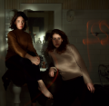 bathroom mirror darkness chiaroscuro flash shadows two young women girls barefoot sweaters stare gaze intense surreal portrait