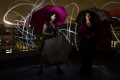 light portrait digital photography dark light chiaroscuro contrast flash streak glow blur rooftop urban umbrellas pink holding laughing two girls young women