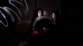 light portrait digital photography dark light chiaroscuro contrast flash streak glow blur two young women holding peacock fan feathers staring confrontational looking each other girls