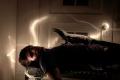 light portrait dark shadow lighting streak blur flash young man brunette boy lying chest steamer trunk old fashioned studs morgue dead lizard reptile chest creepy weird body shadows chiaroscuro