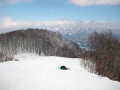 photograph of a skiier lying down on a snow covered slope panorama clouds white lone lonely solitary strange funny bizarre composition nature