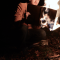 digital photograph evening dusk young man holding up reading book in flames burning fire bonfire campfire autumn fall dried leaves bare trees branches brown corduroy jacket