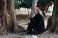 young man black jacket park nature woods sitting pensive