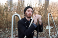 young man black jacket beanie hat park nature woods bicycle rack pose metal