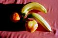 film photograph still life bananas orange pear clementine tangerine pink cloth shadow chiaroscuro contrast light