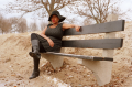 young african american woman girl park bench winter bare branches sand beach black dress LBD sun hat fashion boots leather