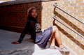 young woman girl african american dress sitting steps black leather jacket
