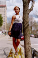young woman girl african american dress white lace standing on traffic barriers tree