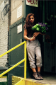 young woman girl model brunette wavy hair holding bouquet purple flowers