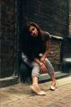 young woman girl model brunette wavy hair alleyway