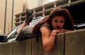young woman girl model brunette wavy hair black lipstick grey dress lying on stomach