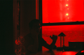 film photograph portrait red filter young man sitting kitchen window reflection mardi gras beads