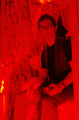 film photograph red filter young man sitting bathroom shower curtain holding cup glasses drink me