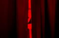 film photograph red filter young man curtain gap peeking through
