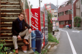 film photograph portrait young man red hair ginger blue scarf handsome sitting rusty stairs coke machine vending street