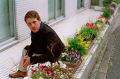 film photograph portrait young man red hair ginger blue scarf handsome sitting flowers colorful