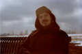 film photograph portrait young man goatee beard mustache sitting bench winter hazy sky russian cap hat earflaps pensive