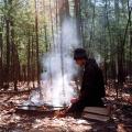 film photograph portrait camping fire pit smoke chiaroscuro young man sitting tending peaceful