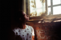 film photograph portrait chiaroscuro light shadow young man looking out window graffiti bricks