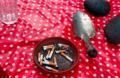 film photograph still life ashtray cigarettes dish polka dot red tablecloth shovel spade rocks water glass