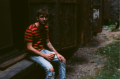 film photograph portrait young man sitting striped tshirt rusty doors starbucks red holiday cup