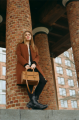 film photograph portrait young woman long hair blonde bokeh brick pillar standing handbag purse
