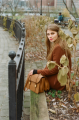 film photograph portrait young woman long hair blonde bokeh sitting park handbag leather