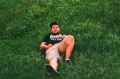 film photograph portrait young man lying down lawn grass green plants summer chicago vape nation cvn