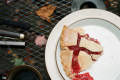 film photograph piece of pie strawberry rhubarb plate table autumn leaves