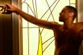 photography digital light dark chiaroscuro contrast portrait stained glass window yellow backlit shirtless topless chain golden chest young african american black man buff confident gaze pointing glow