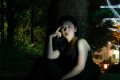 photograph digital light portrait dark contrast shadow chiaroscuro flash streak blur glow outside outdoors trees foliage urban light kitsune jinja shrine japan red young asian woman red lipstick pensive leaning trunk thinking surreal mysterious