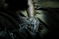 digital photograph dark light chiaroscuro shadows streak blur creepy black surreal bizarre saran wrap plastic wrapped hands fingers spread reaching bed bedcover quilt green SM bondage games kinky play