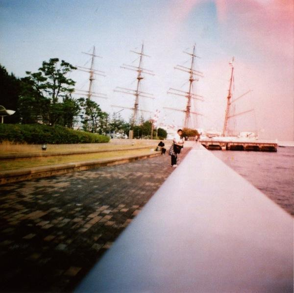 film photograph bay ship masts water ocean magical fantasy sea pink blue sky clouds lomography