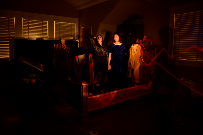 bedroom empty bed frame mannequins clothes clothing two young women girls holding hands blue dress flash streak blinds holding hair back mysterious surreal light