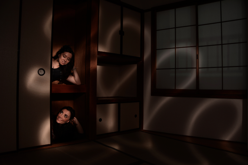 light portrait digital photography dark light chiaroscuro contrast flash streak glow blur japanese tatami room traditional paper windows oshiire closet sliding door two girls young women smiling looking each other surreal weird bizarre