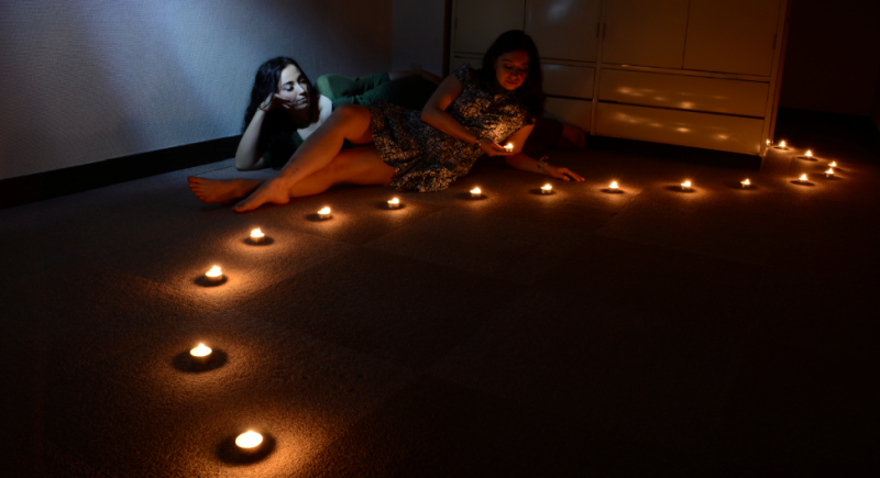 light portrait digital photography dark light chiaroscuro contrast flash streak glow blur two young women girls reclining lying down tea lights line curve arrangement holding reflective pensive cute romantic warm lighting