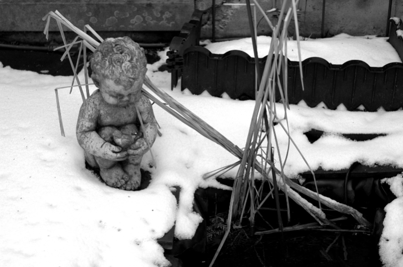 black and white digital photograph cupid statue snow winter pond reeds fountain garden forlorn cold