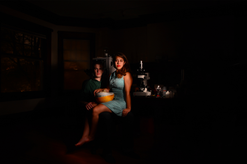 light portrait photography long exposure chiaroscuro dark shadow contrast light swirl glow streak strange bizarre surreal young woman man posing couple brunette blond sitting lap bowls stack garlic yellow kitchen mixing blue dress retro red lipstick lap equipment wine glass microscopes surreal green shirt