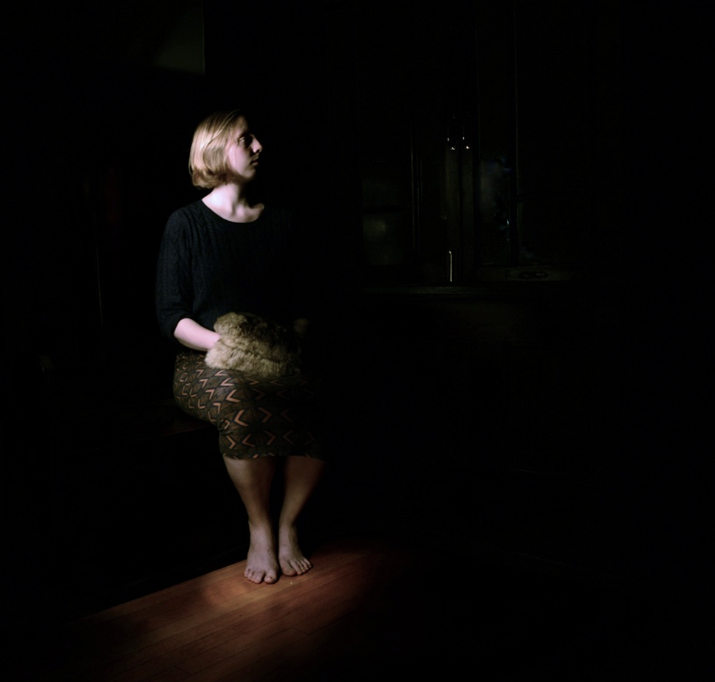 light portrait photography muff fur young woman girl blonde short hair bob skirt sitting bare feet dark chiaroscuro contrast forlorn waiting strange bizarre surreal