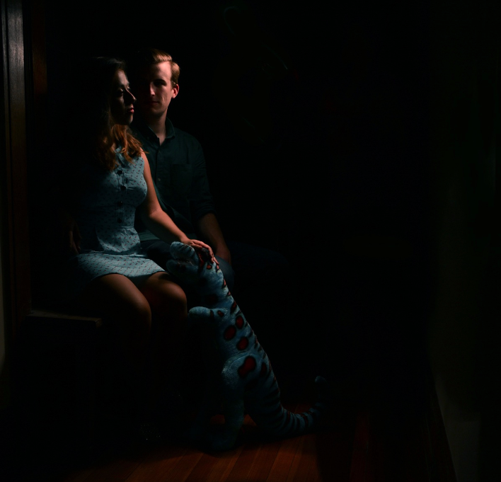 light portrait photography long exposure chiaroscuro dark shadow contrast light swirl glow streak strange bizarre surreal couple young man woman brunette blond blue dress retro dinosaur stuffed animal petting hand head spots purple cute weird