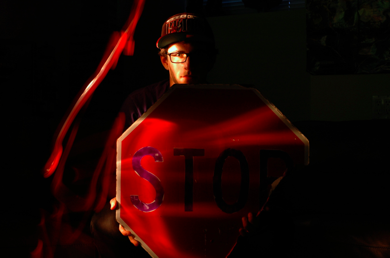 light portrait photograph dark streak red stop sign broken torn young man boy glasses baseball hat chiaroscuro chicago bulls holding strange