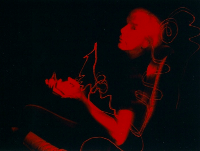light portrait photography long exposure chiaroscuro black light contrast man holding sitting questioning strange surreal red swirls streaks