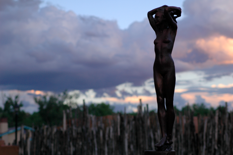 digital photograph woman statue female figure naked arms raised holding head sunset clouds trees wooden fence peaceful beautiful nature bronze