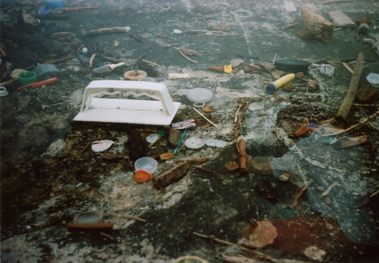 film photograph double exposure trash ground dirt stone bottle caps tampon applicators plastic twigs sticks jumble mess