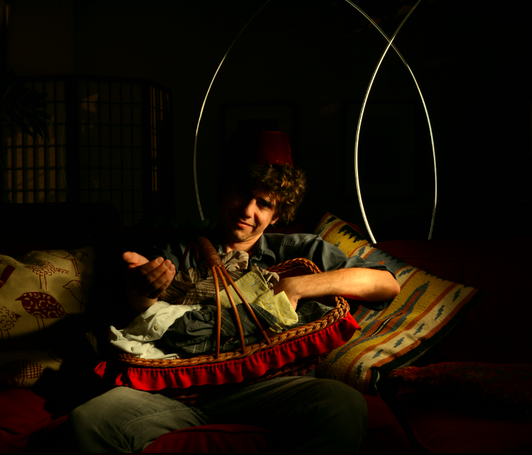 digital photograph light portrait chiaroscuro dark light contrast flash glow creepy surreal weird bizarre strange modern young man dark hair brunette boy turkish fez curly hair holding hand reaching beckoning basket red laundry clothes ruffle sofa cushions couch