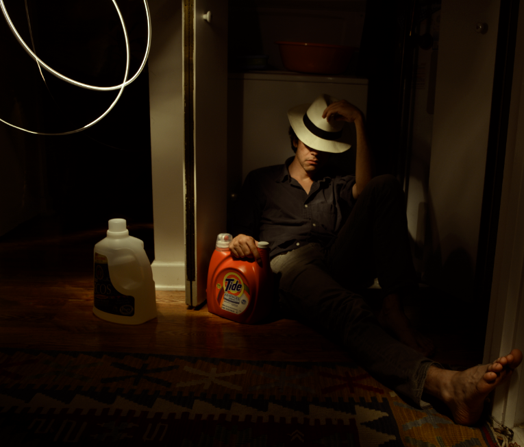 digital photograph light portrait chiaroscuro dark light contrast flash glow creepy surreal weird bizarre strange modern young man dark hair brunette boy white hat cowboy resting napping holding washing machine tide detergent bare feet perspective distorted stretched out leg