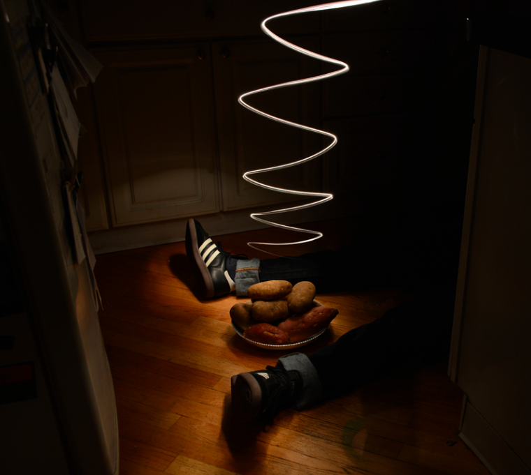 light portrait digital photograph chiaroscuro contrast dark shadow lighting kitchen floor wooden bowl potatoes yams shoes black white stripes jeans legs lying spiral flash streak surreal weird