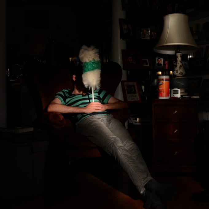 light portrait digital photograph chiaroscuro contrast dark shadow lighting  living room armchair young man boy sitting green tshirt stripes clorox wipes lamp table holding in front of face duster white